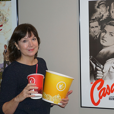 Becky King holding popcorn bucket and drink in front of Casablanca poster